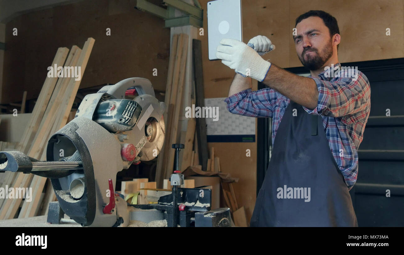 The carpenter makes selfie on tablet in the workshop near electric saw. Professional shot on Lumix GH4 in with high 4K resolution. You can use it e.g  Stock Photo