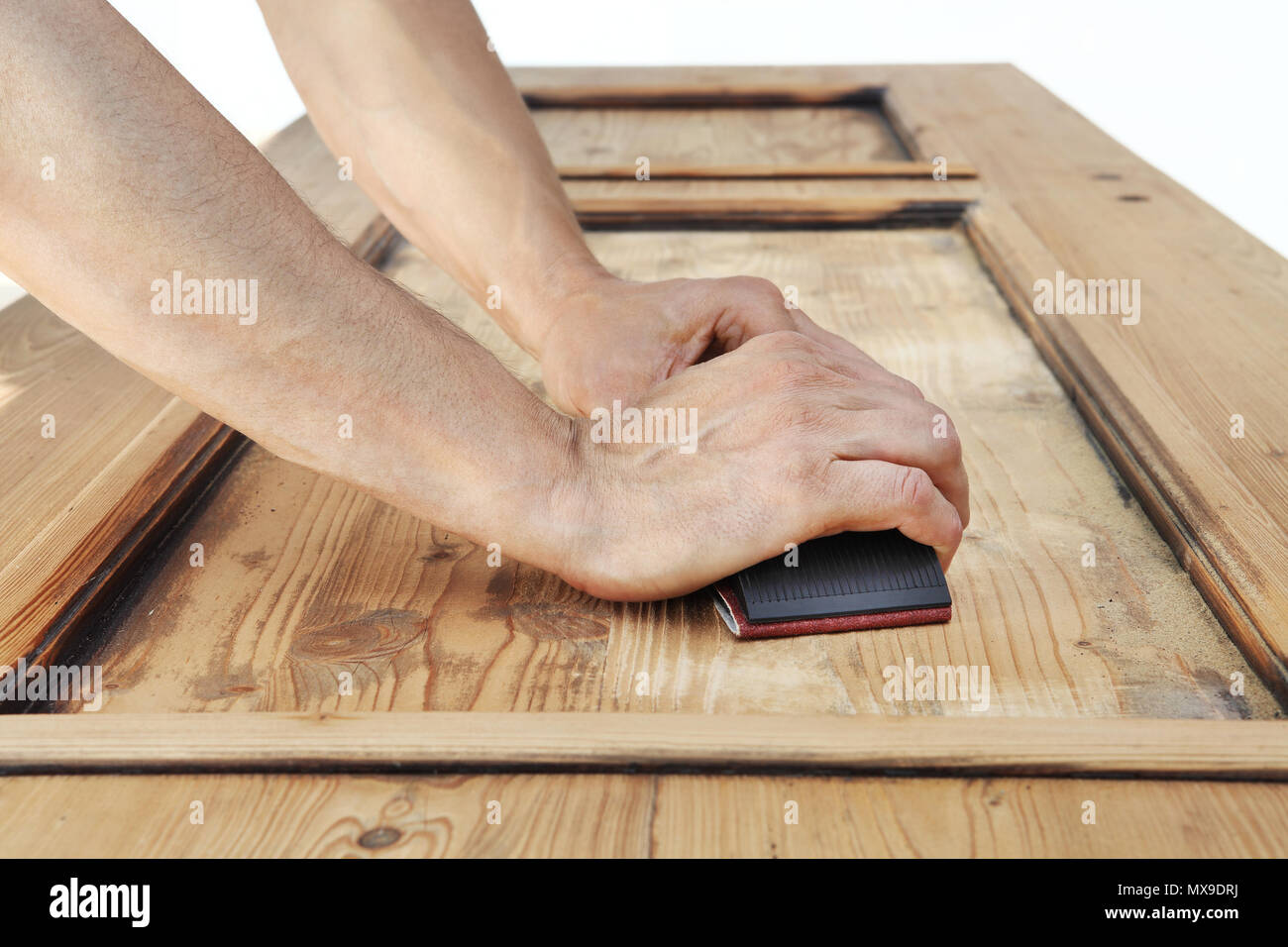 carpenter hands work the wood with the sandpaper - Stock Image