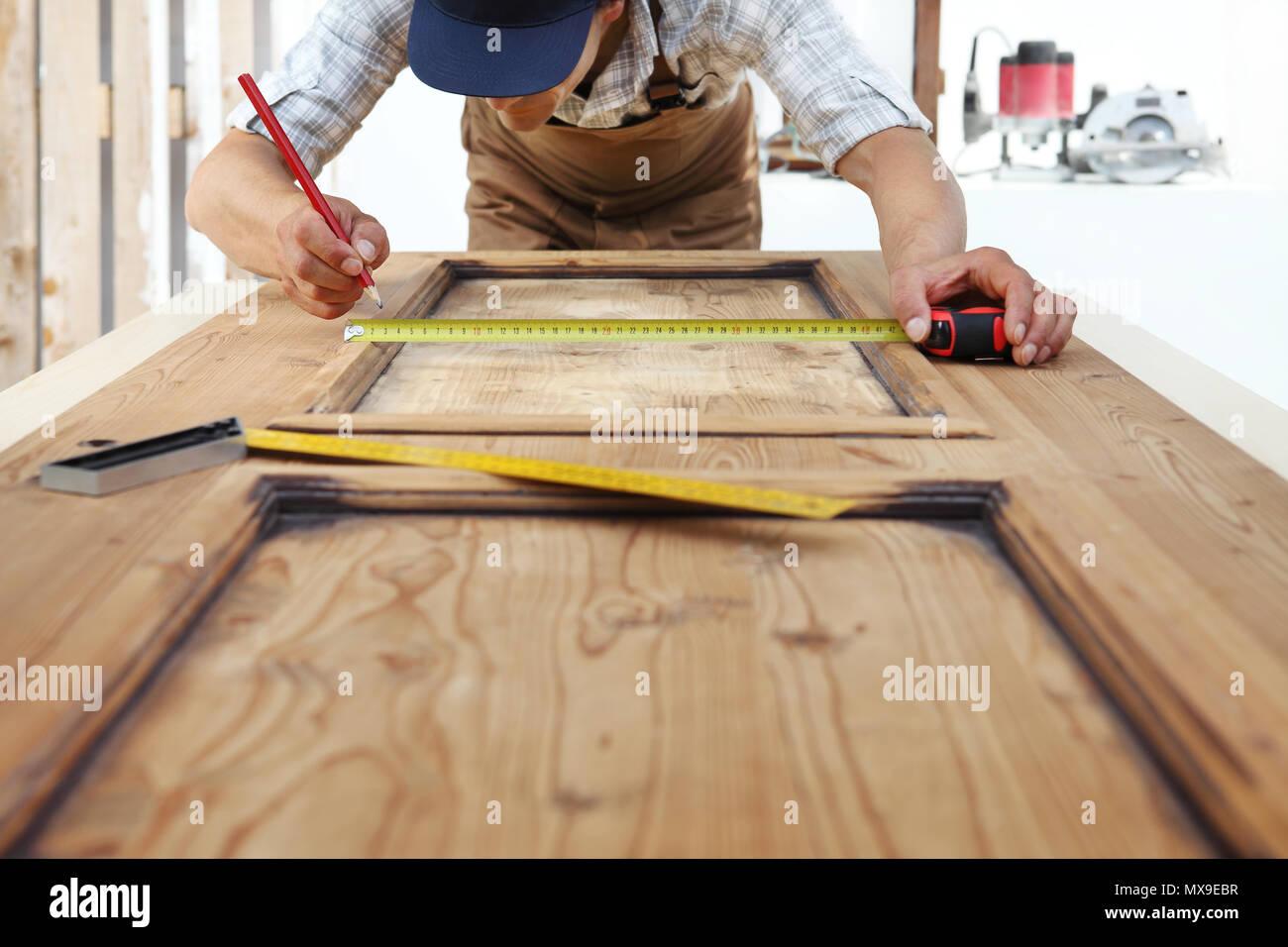 carpenter work the wood, measuring a wooden vintage door Stock Photo