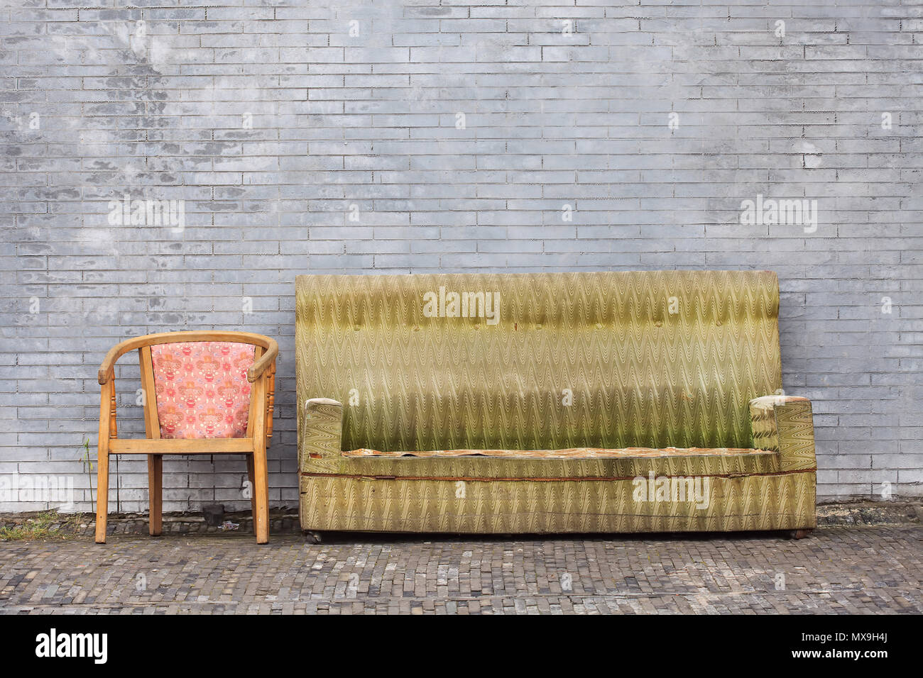 Old worn-out furniture against ta great brick wall, Beijing, China Stock Photo