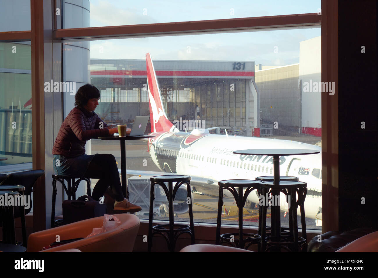 Woman using computer and drinking coffee while waiting for Qantas flight at airport, Sydney, NSW, Australia. No MR or PR - Stock Image