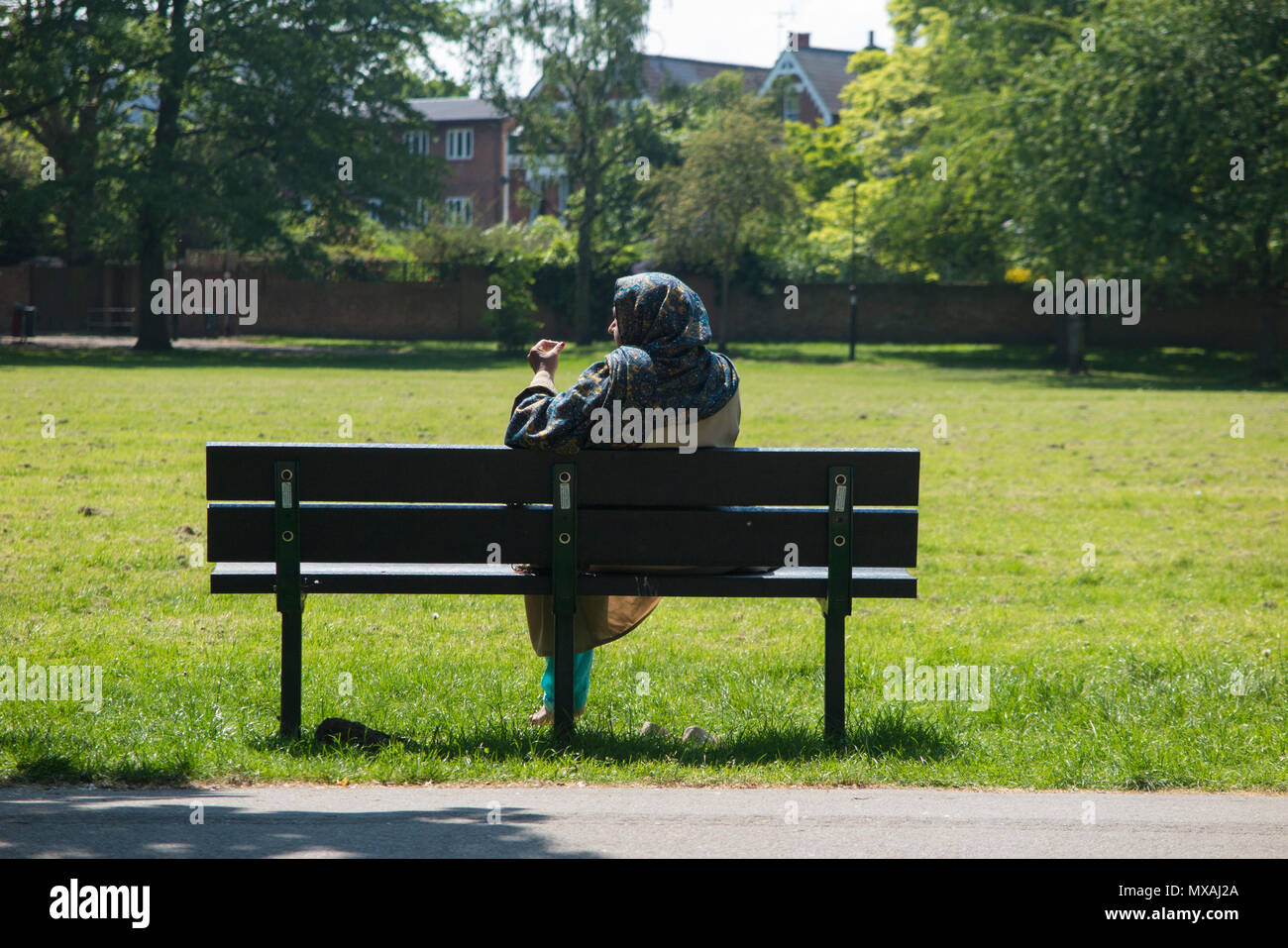 A muslim woman on the phone in a London park - Stock Image