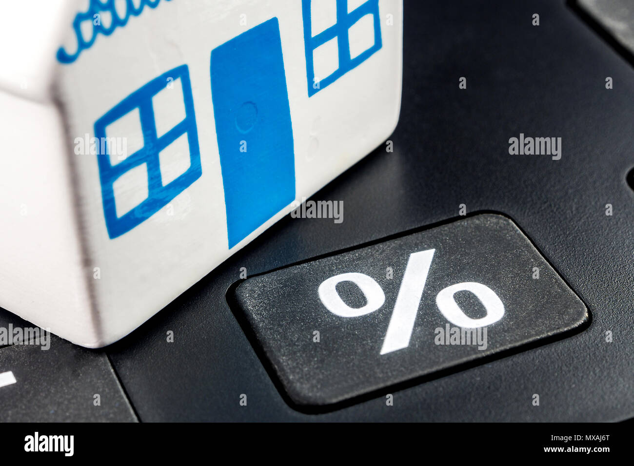 big black calculator with big percentage button and one ceramic miniature of a house Stock Photo