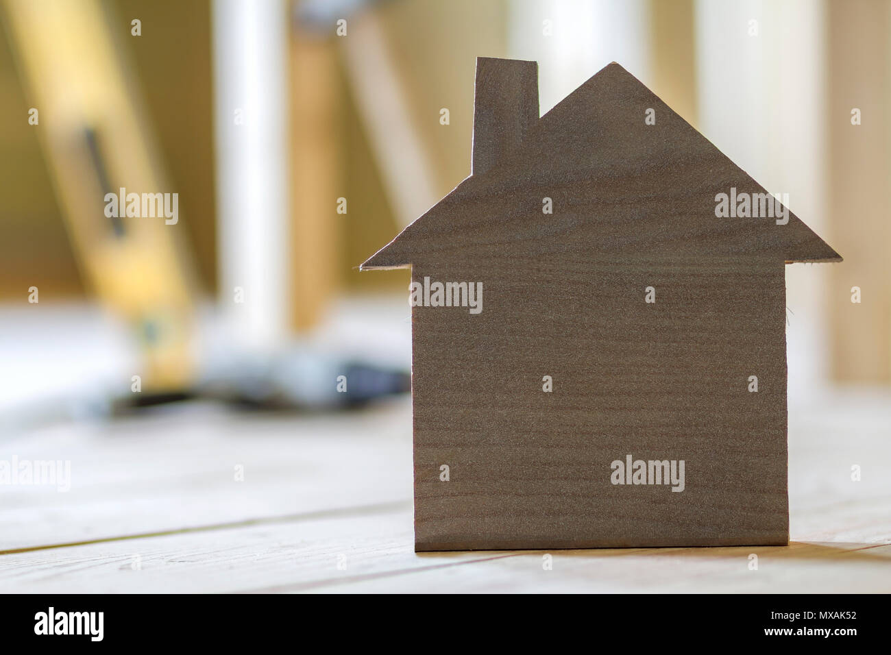 Close-up of simple small brown model house on blurred