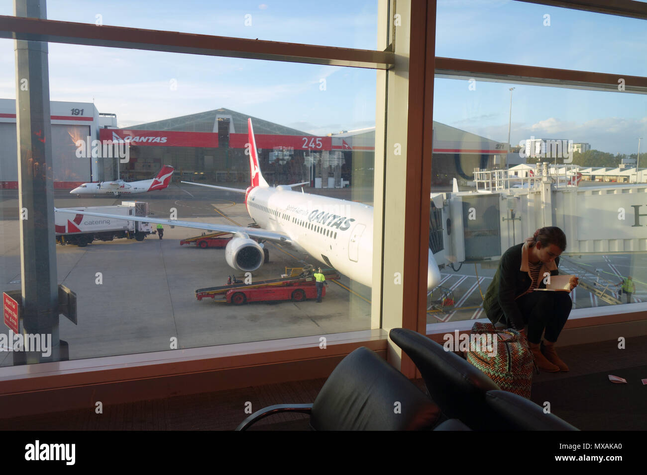 Woman reading a book while waiting for Qantas flight at airport, Sydney, NSW, Australia. No MR or PR - Stock Image