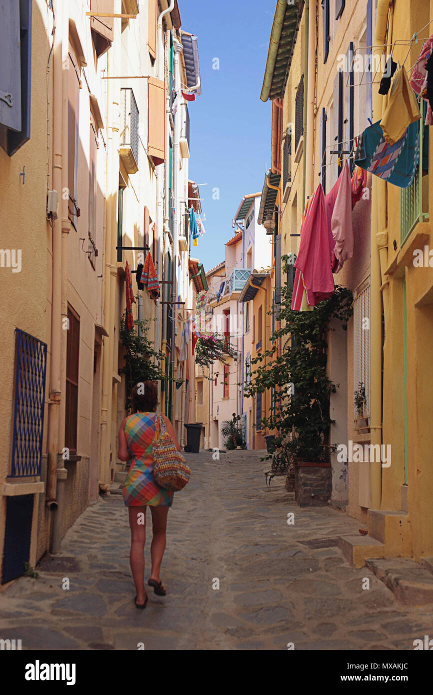 Girl in a brightly-coloured minidress walks down a narrow lane, Rue de la Liberté, in Port d'Avall, Collioure, Occitanie, France.  MODEL RELEASED - Stock Image