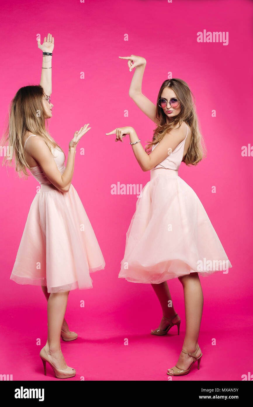 Sisters in pink dresses emotionally posing and pointing by hands. - Stock Image