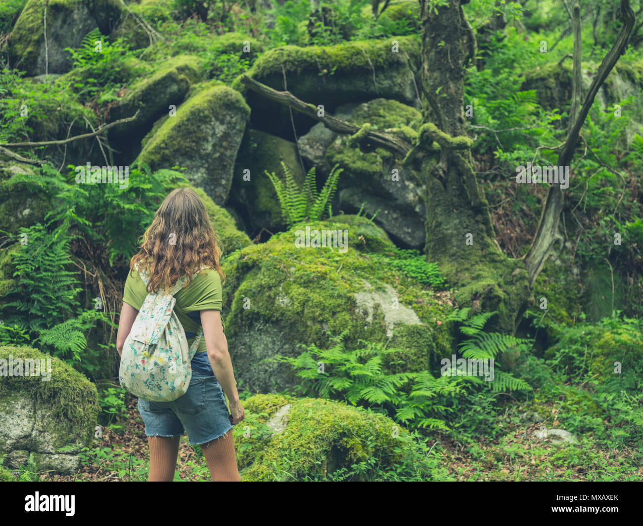 A young woman is walking in the forest - Stock Image