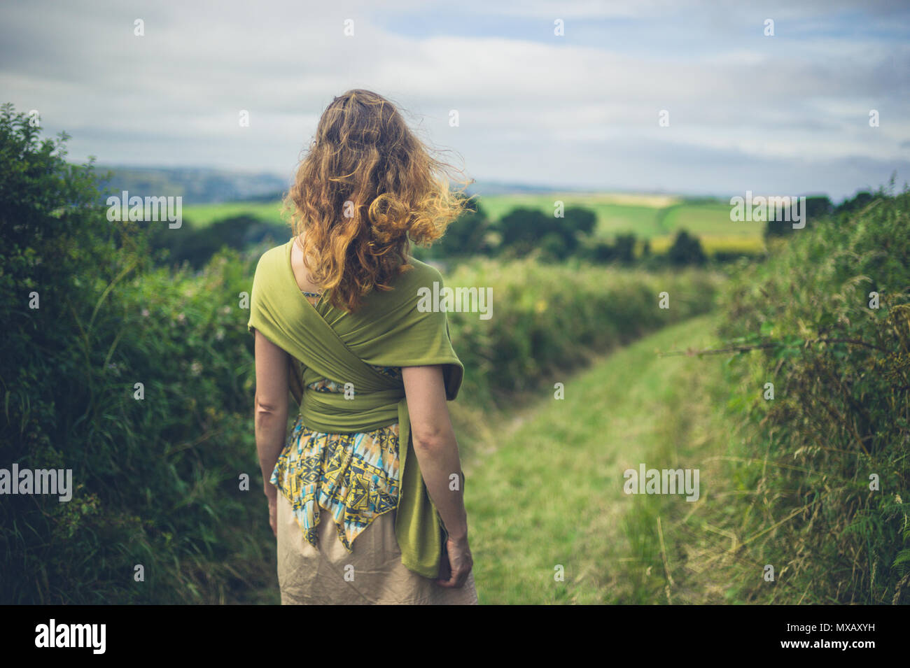 A young woman is walking in the countryside - Stock Image