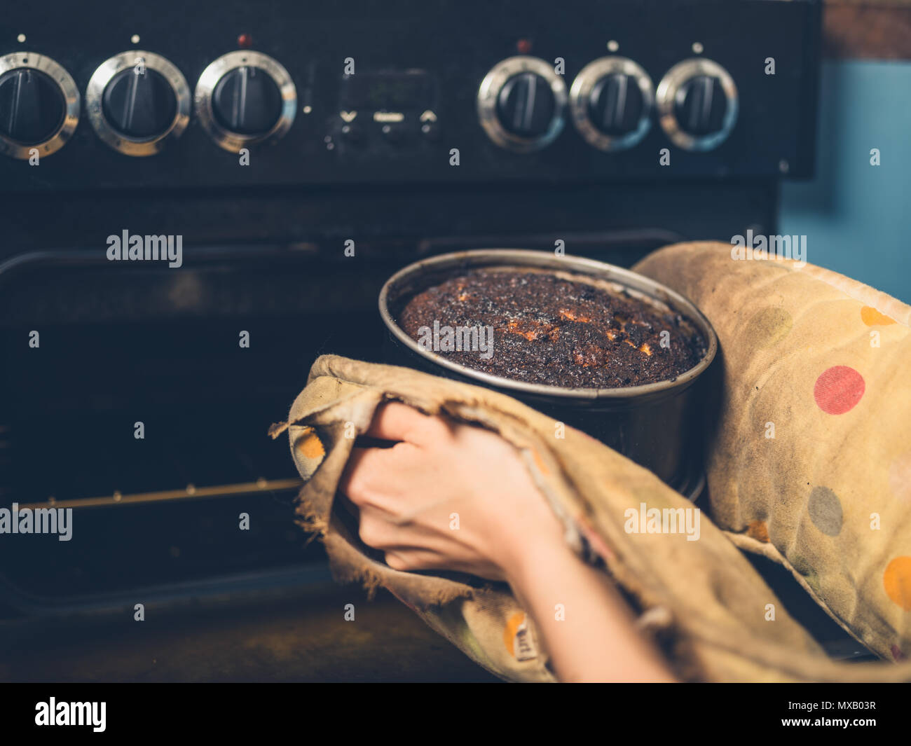 The hands of a woman is removing a burnt cake from the oven - Stock Image
