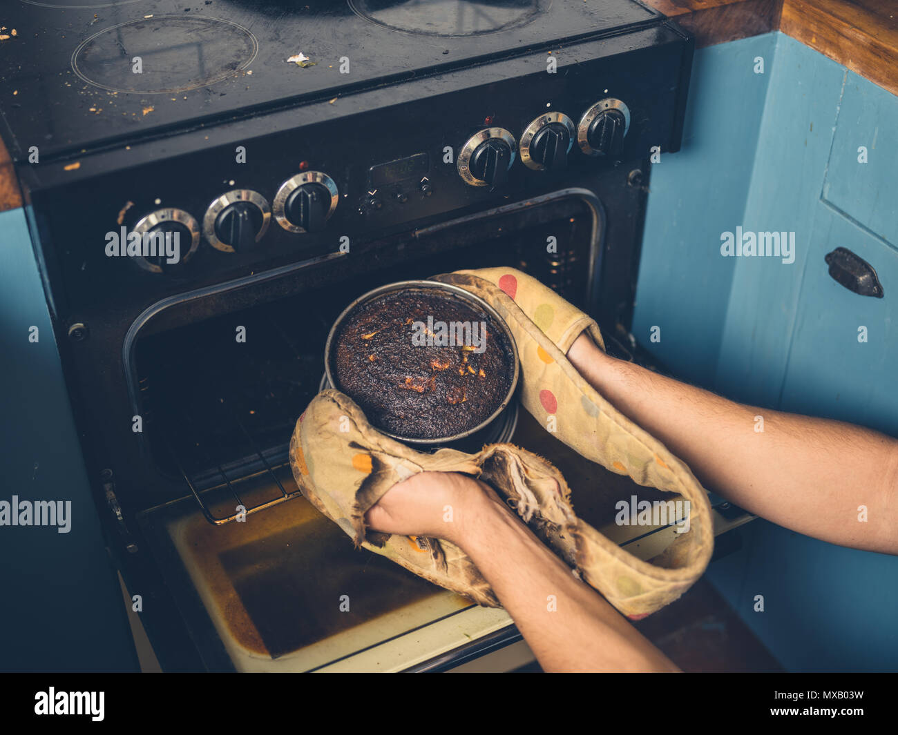 The hands of a man is removing a burnt cake from the oven - Stock Image