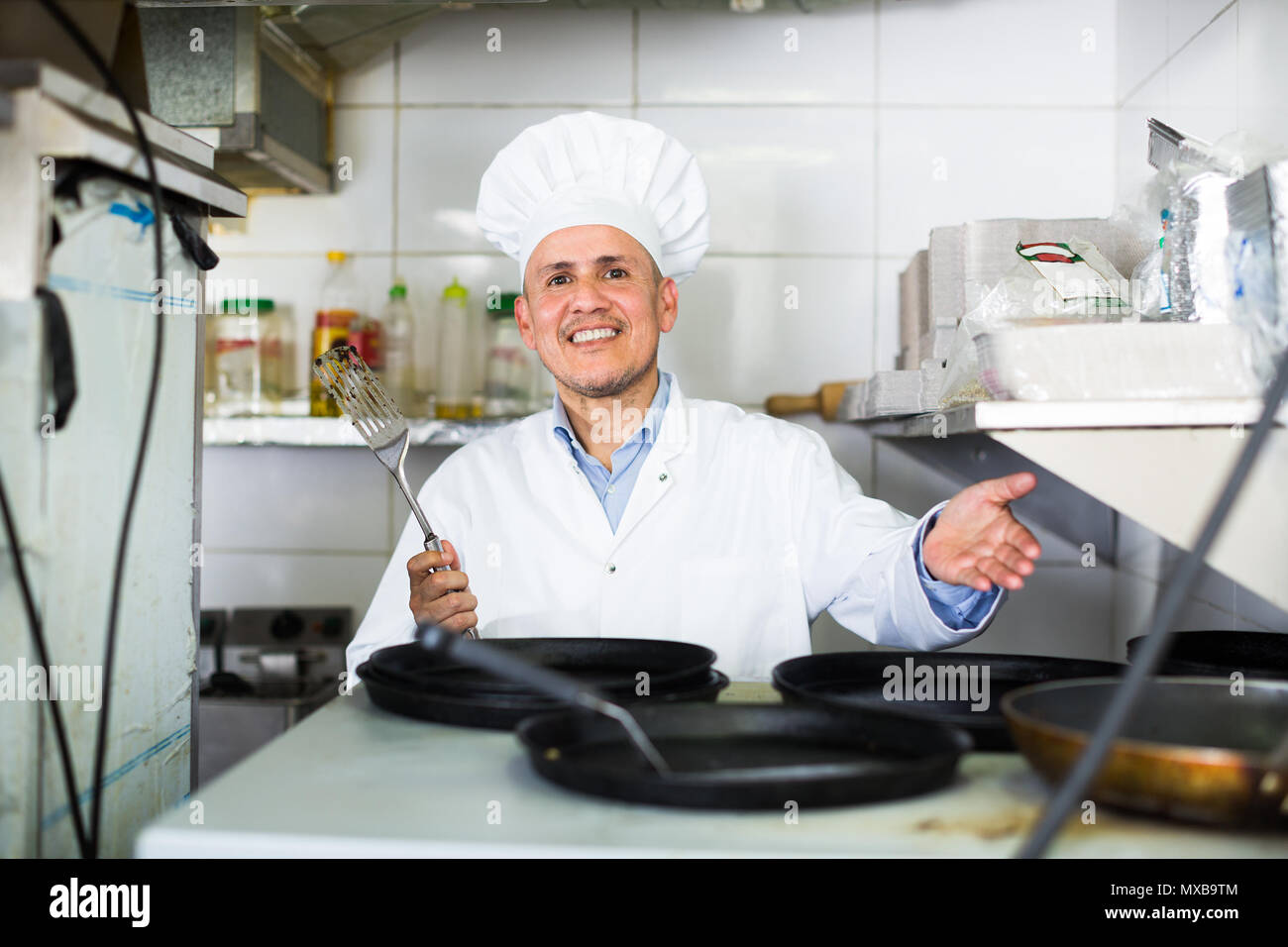 Man professional cook wearing uniform sitting on kitchen with frying ...