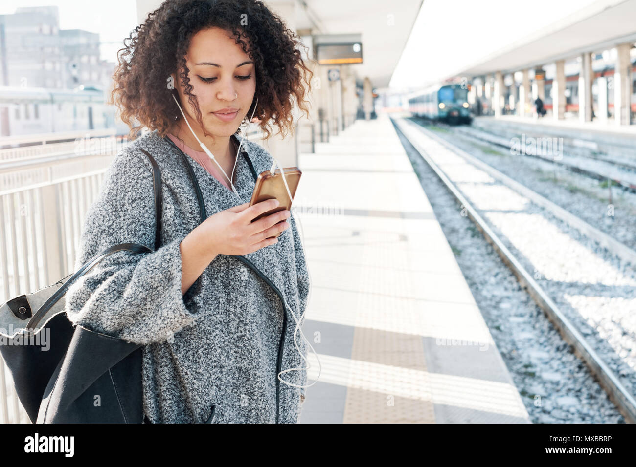 Young black woman waiting for the train on station platform - Stock Image