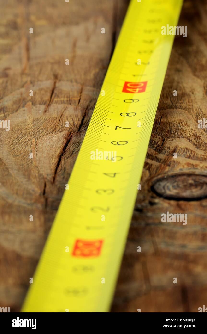 Yellow metallic decimal tape measure on wooden background. Selective focus. - Stock Image