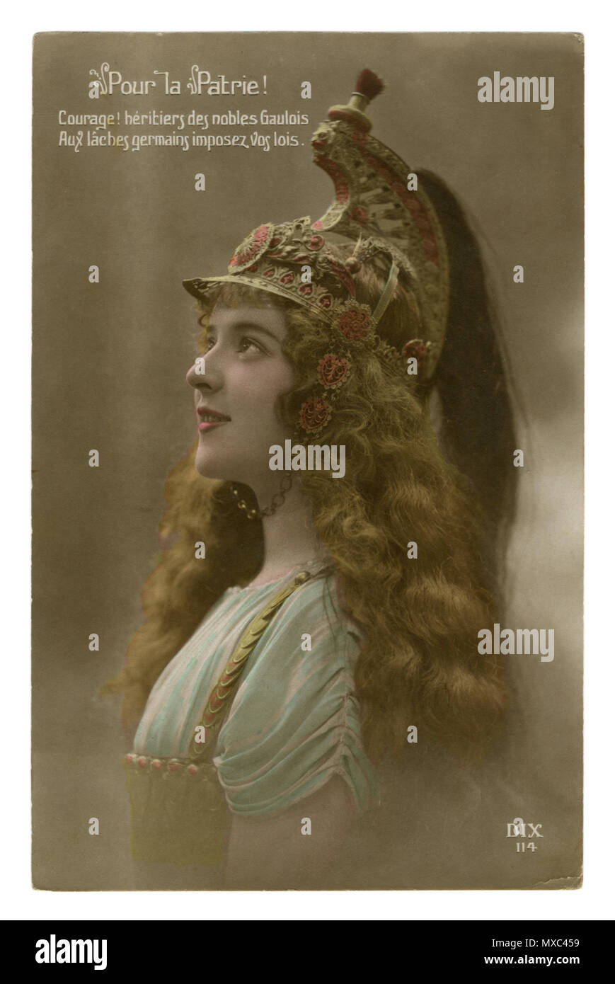French historical colored photo postcard: A beautiful young girl with long wavy hair in a patterned cavalry helmet with plumage. world war one 1914-18 - Stock Image