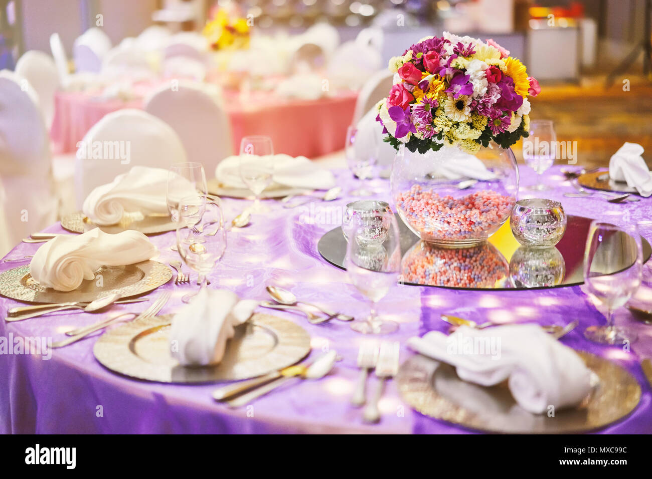 The closeup shot of dinner table setting with a big glass vase of the closeup shot of dinner table setting with a big glass vase of flower bouquet decoration izmirmasajfo