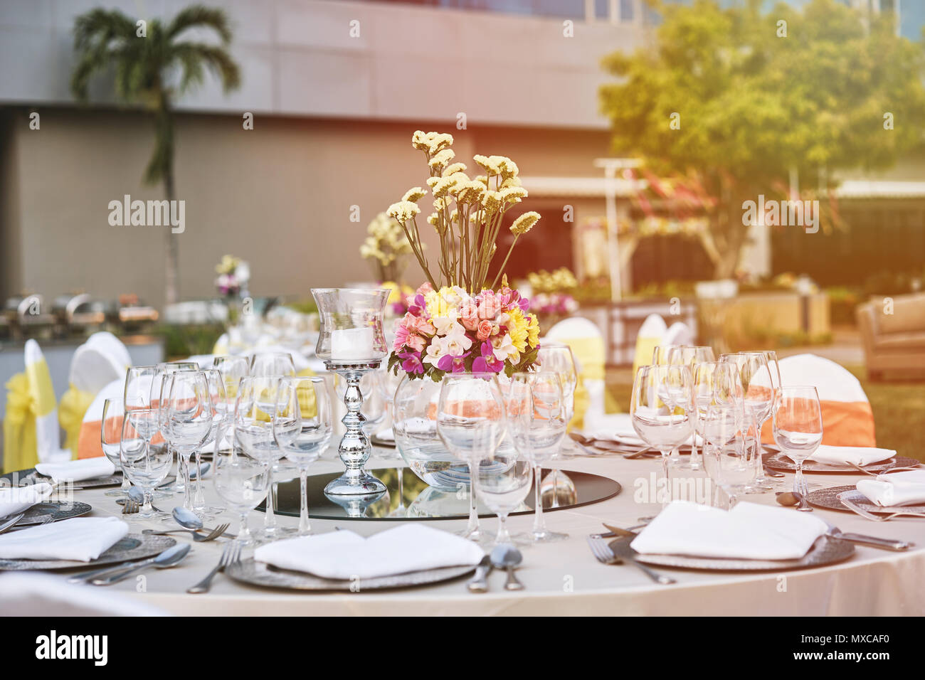 Wedding Reception Dinner Table Setting With Empty Glasses Of Water, Wine  And Dinnerwear With Flower Decoration, And White Fabric Cover Chairs With  Yel
