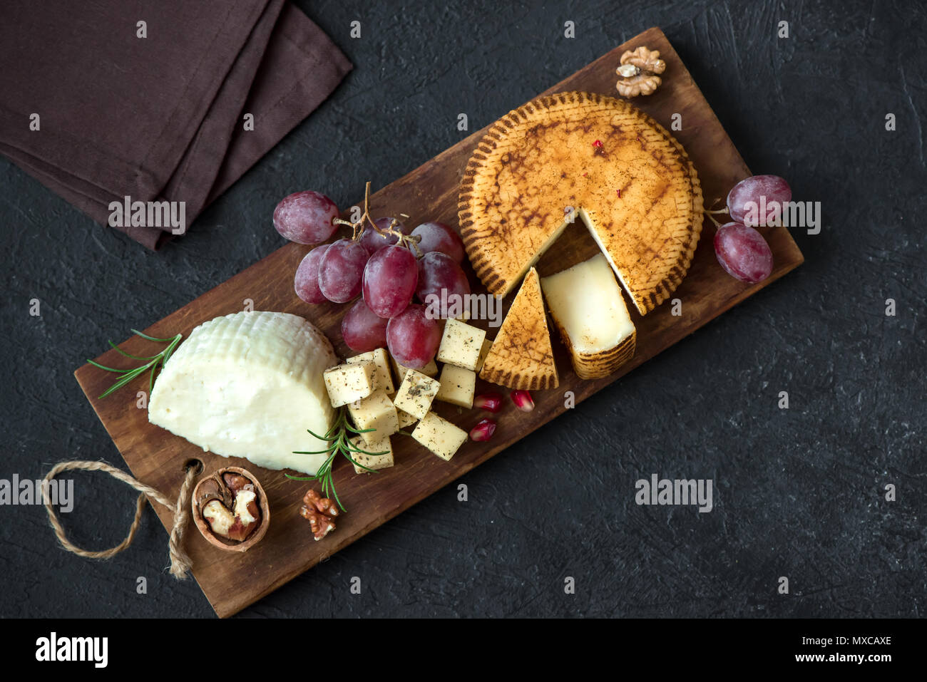 Cheese platter with assorted cheeses, grapes, nuts over black background, copy space. Italian cheese and fruit platter. - Stock Image