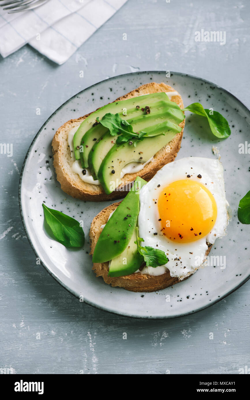 Avocado Sandwich with Fried Egg - sliced avocado and egg on toasted bread for healthy breakfast or snack, copy space. - Stock Image