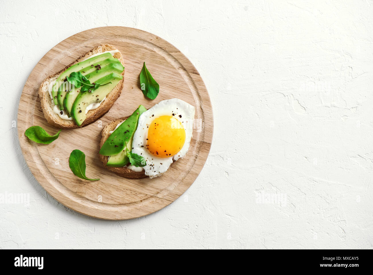 Avocado Sandwich with Fried Egg - sliced avocado and egg on toasted bread for healthy breakfast or snack, copy space. Stock Photo