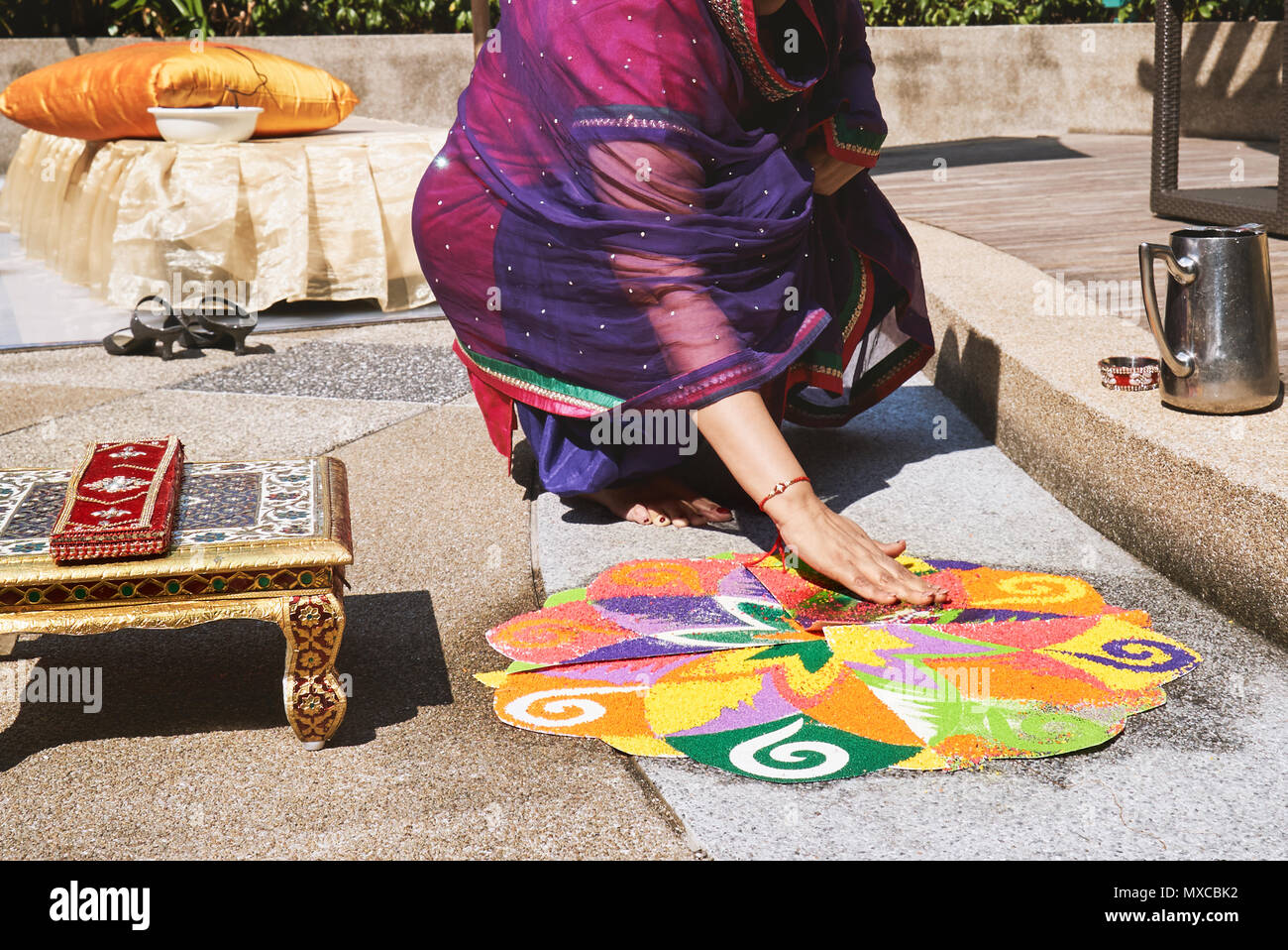 Women decorating and coloring tradition colorful rice art or sand art (Rangoli) on the floor with paper pattern using dry rice and dry flour with colo Stock Photo