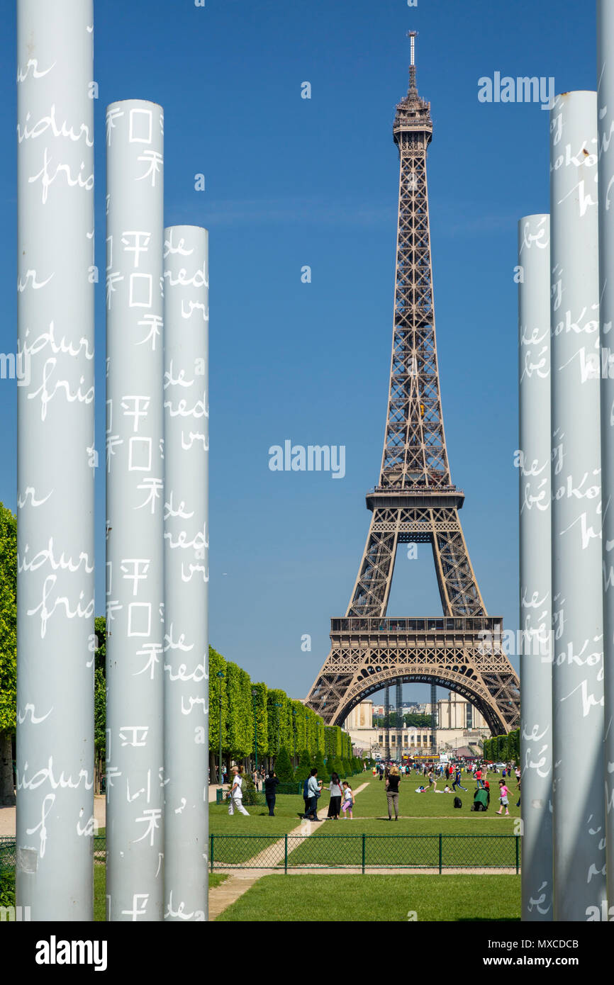 View along Champ de Mars of the Eiffel Tower through the columns of the Peace Memorial, Paris, France - Stock Image