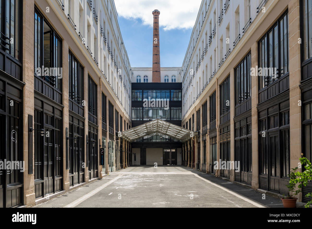 Old industrial factory and chimney, converted to modern offices along Rue du Faubourg-Saint Antoine, Paris, France - Stock Image