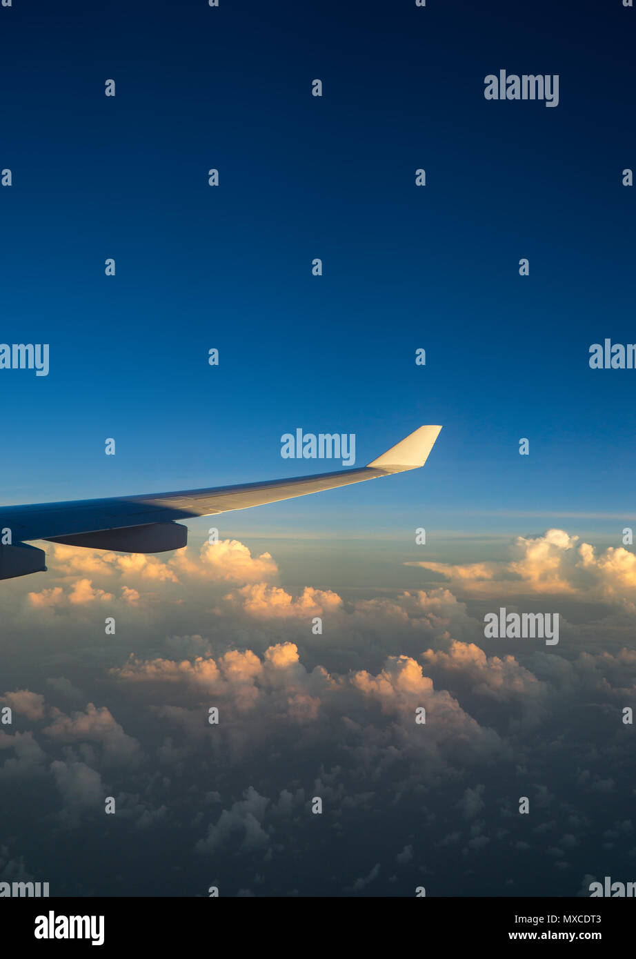 View out of airplane window with clouds at sunset and airplane wing. Stock Photo