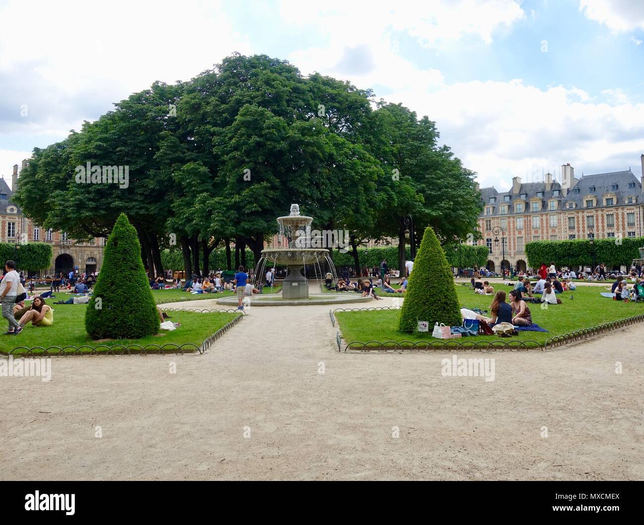 People sitting, lying on the grass and enjoying Place des Vosges, in the 3rd/4th Arrondissements, on a warm June afternoon. Paris, France - Stock Image