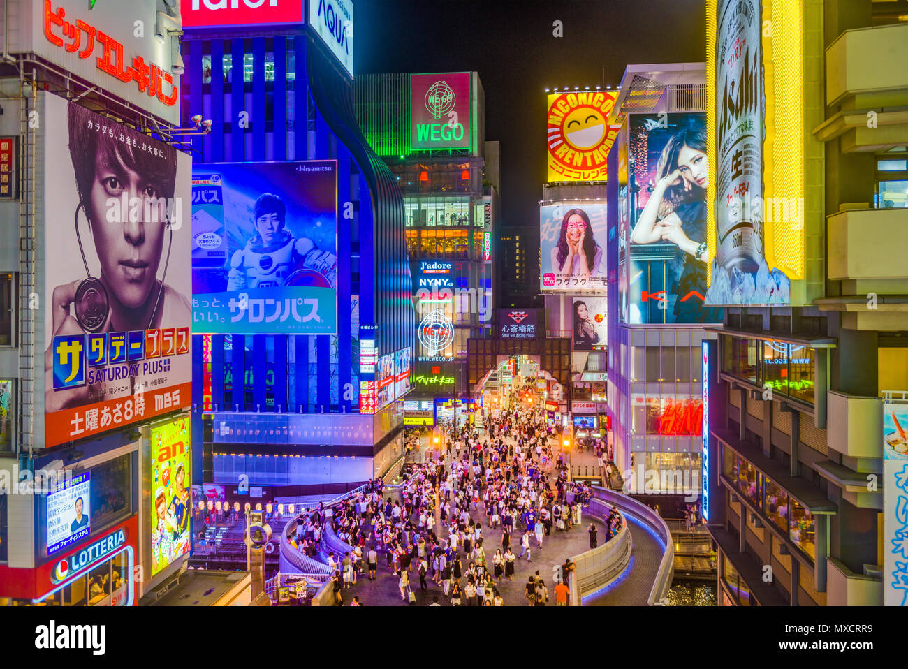 OSAKA, JAPAN - AUGUST 16, 2015: Pedestrians walk below billboards in the Dotonbori district. The district is a popular tourist attraction. - Stock Image