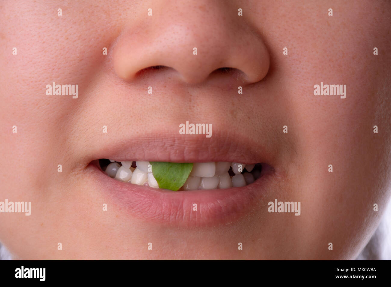 Close-up of woman smiling with spinach or salad stuck in her teeth - Stock Image