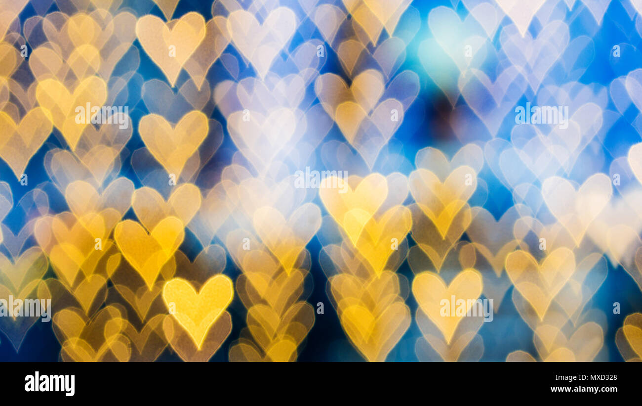 beautiful bokeh made of warm orange blurred lights in the form of hearts on blue background, special photo technique Stock Photo
