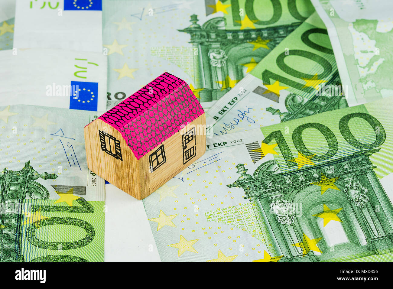 one miniature wooden house laying on one hundred euro banknotes - Stock Image