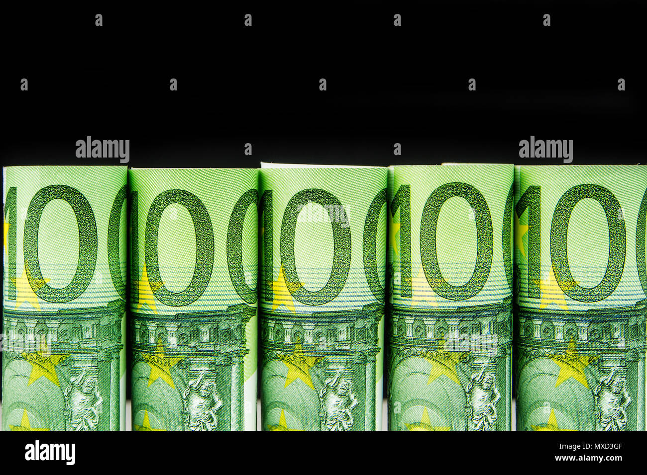 five one hundred euro banknote rolls in one row on black background - Stock Image