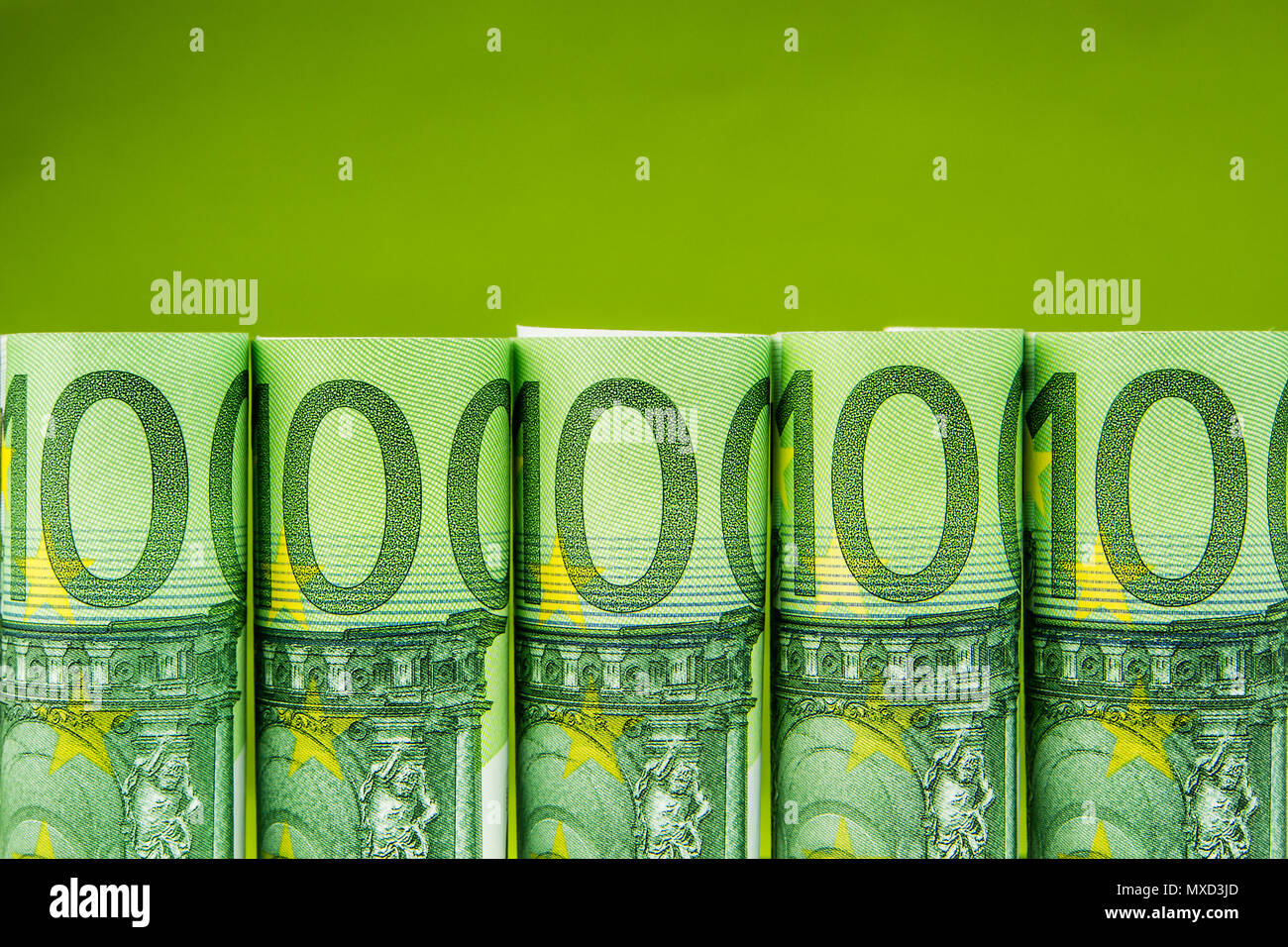 five one hundred euro banknote rolls in one row on green background - Stock Image