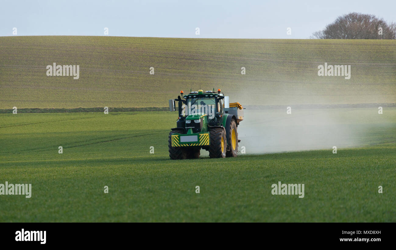 A farmer spreading fertiliser with a tractor and spreader - Stock Image