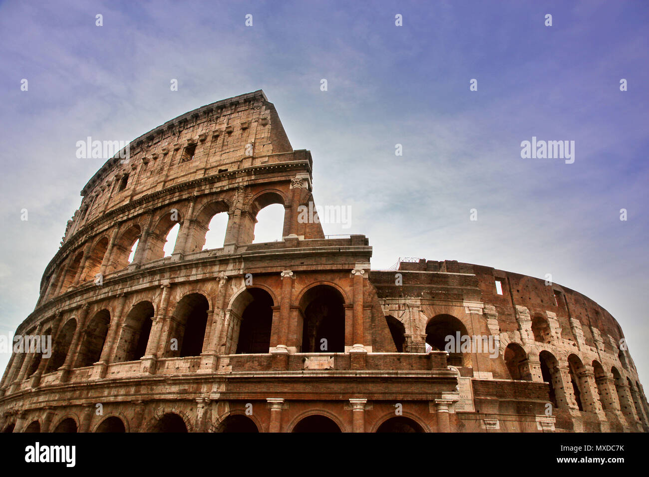 Famous Roman Coliseum against a blue early morning sky - Stock Image