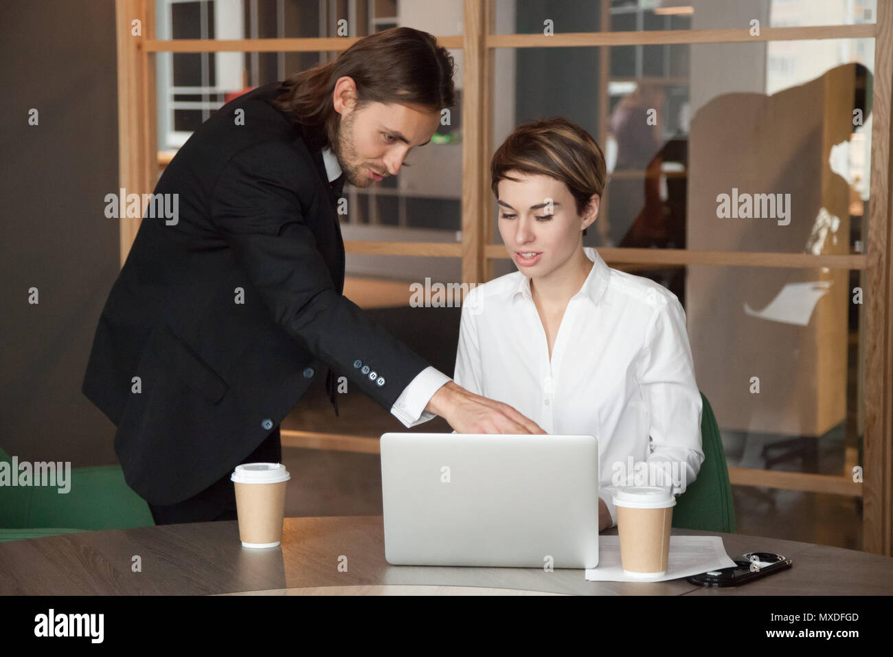 Male leader helping partner assisting with online startup - Stock Image