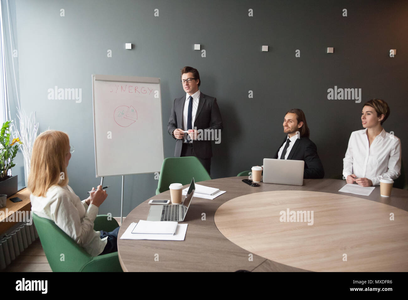 Serious male coach giving presentation on flipchart to business  - Stock Image