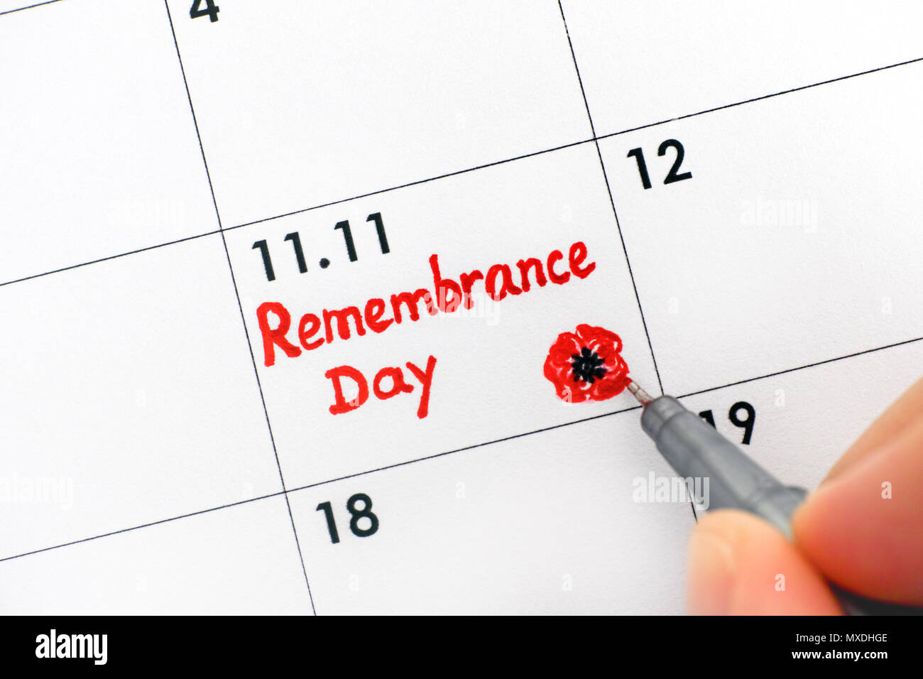 Woman fingers with pen writing reminder Remembrance Day in calendar. Close-up. - Stock Image