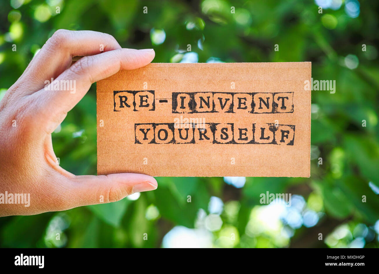 Woman hand holding cardboard card with words Re-Invent Yourself made by black alphabet stamps against green nature background. - Stock Image