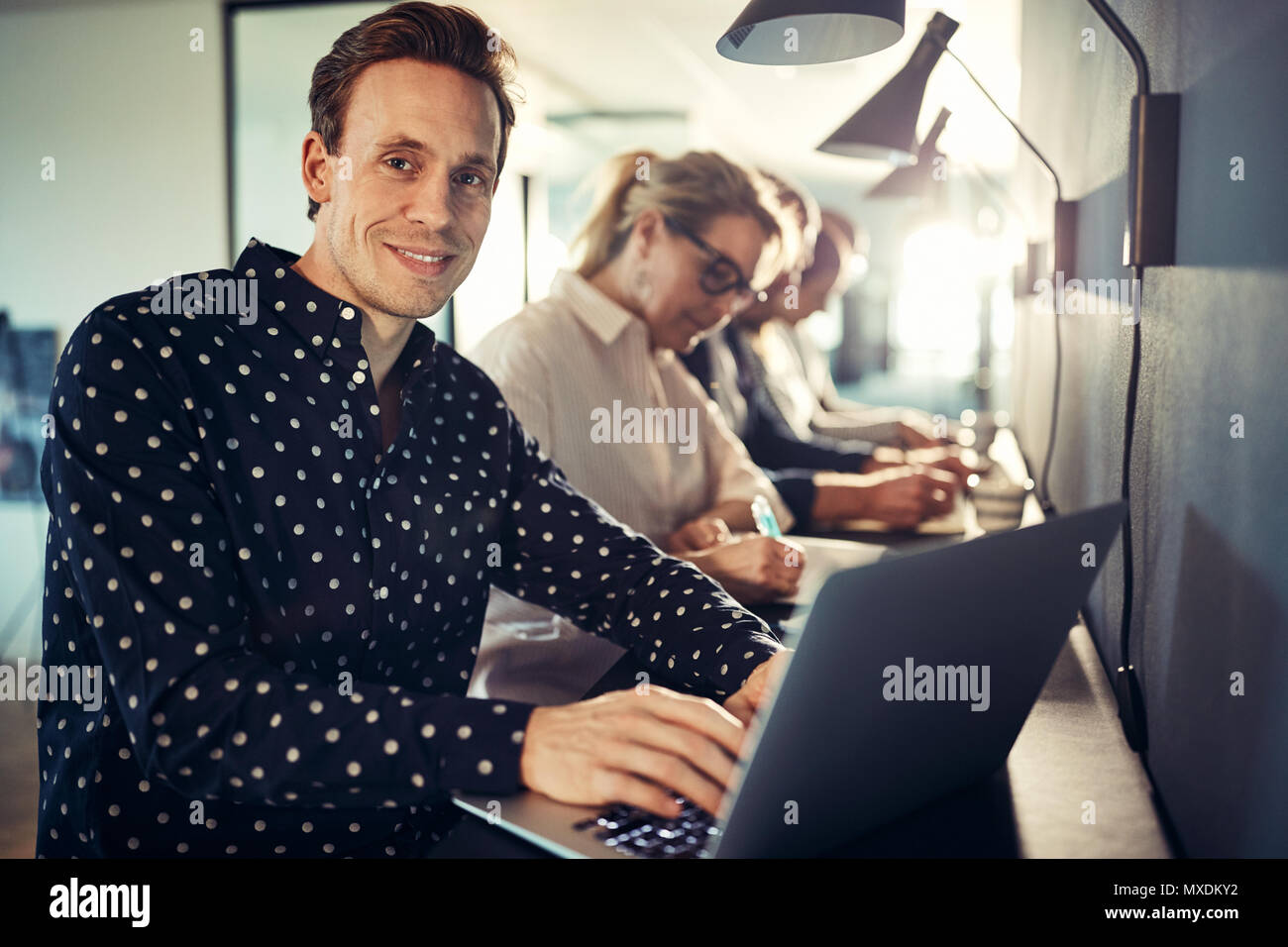 Smiling young designer working on a laptop while sitting in a row with coworkers at a table in a modern office - Stock Image