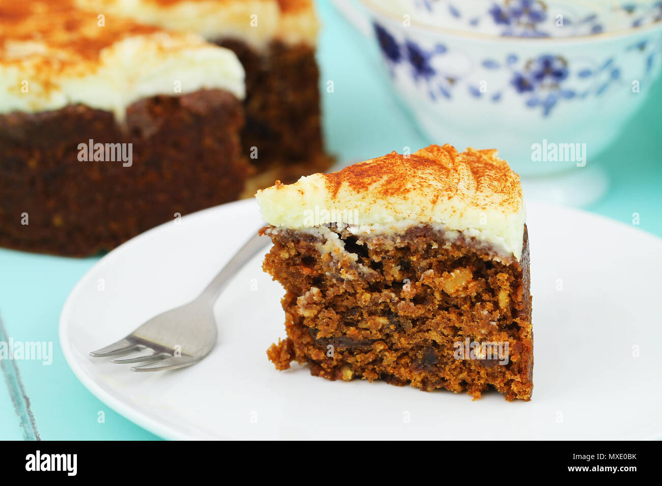 Slice of delicious carrot cake with marzipan icing on white plate Stock Photo