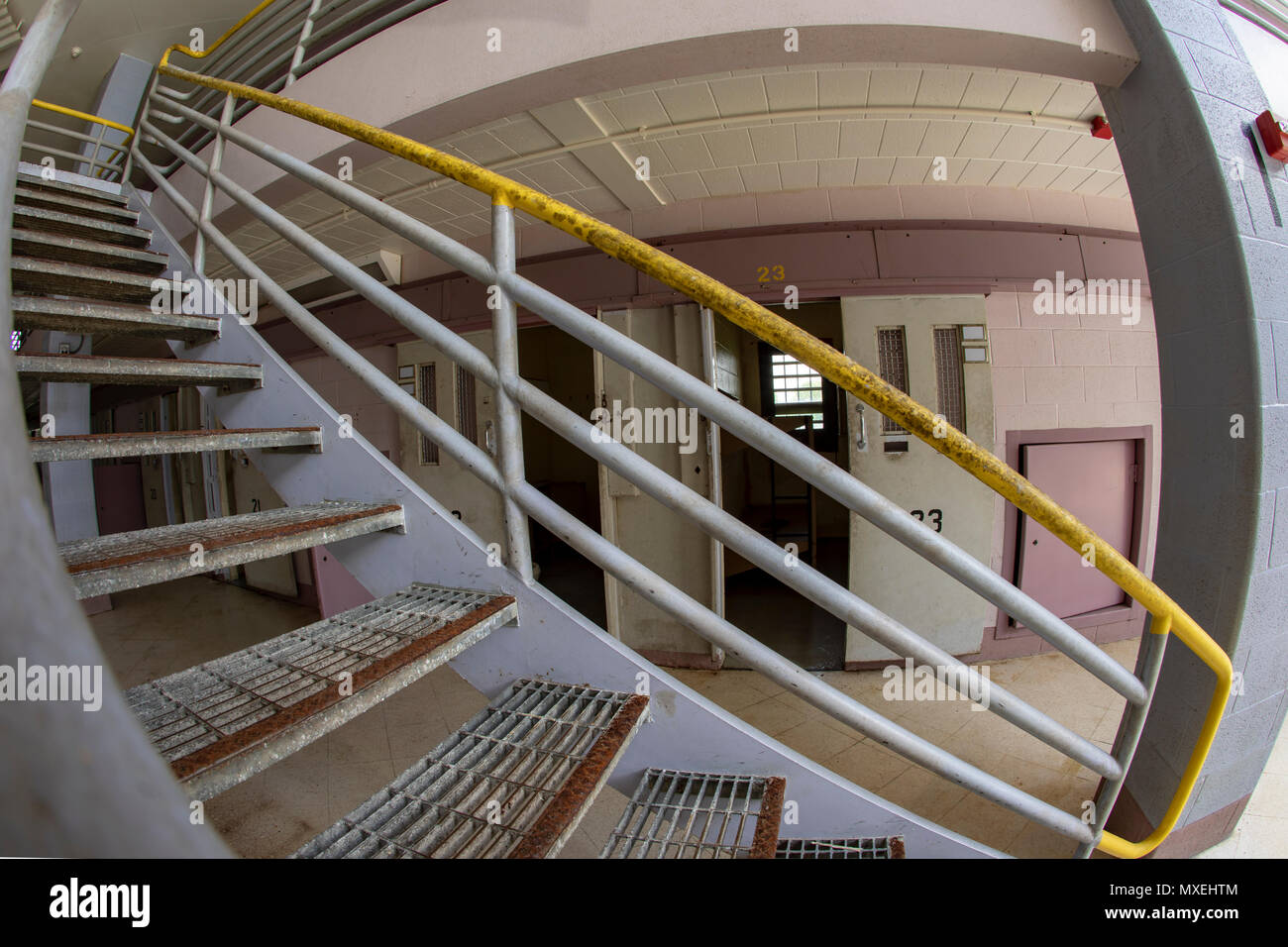 Metal stairs outside open cell doors in cellblock of old prison. - Stock Image