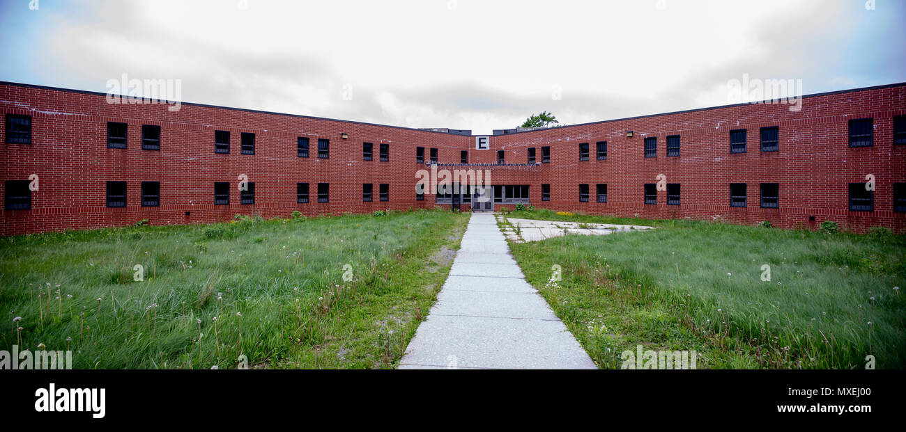 Exterior of brick cellblock with overgrown yard in abandoned prison. - Stock Image