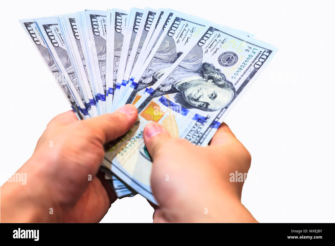 Fan of One Hundred Dollars notes in man hands, isolated on white background with clipping path - Stock Image