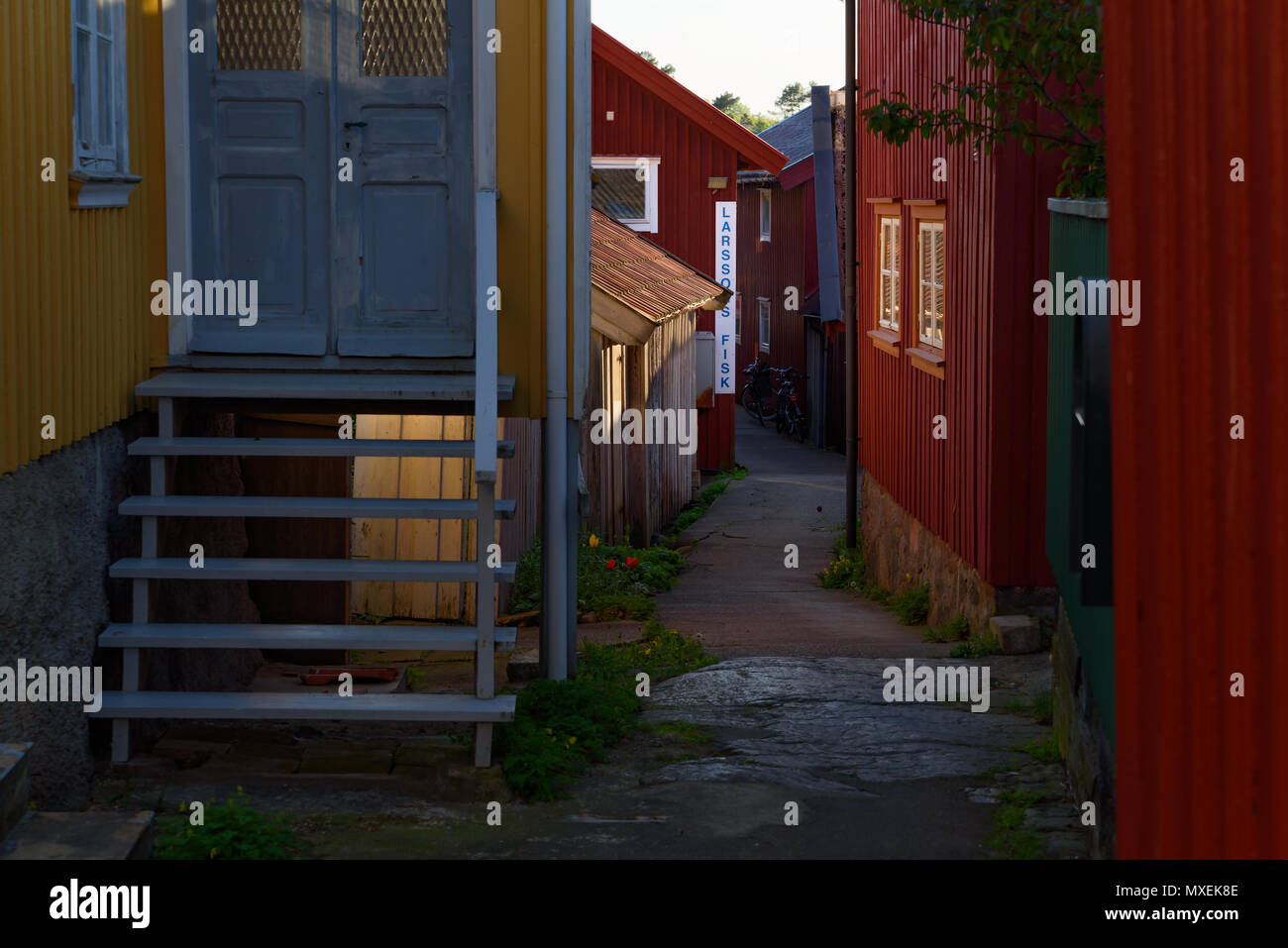 Mollosund, Orust, Sweden - May 18, 2018: Travel documentary of everyday life and place. Small village alley with a fish store at the end. The evening  Stock Photo