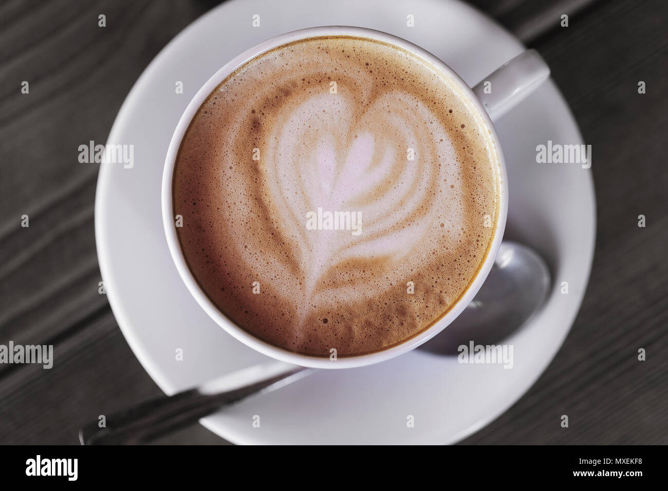 Cup of hot cappuccino coffee on a wooden table, top view - Stock Image