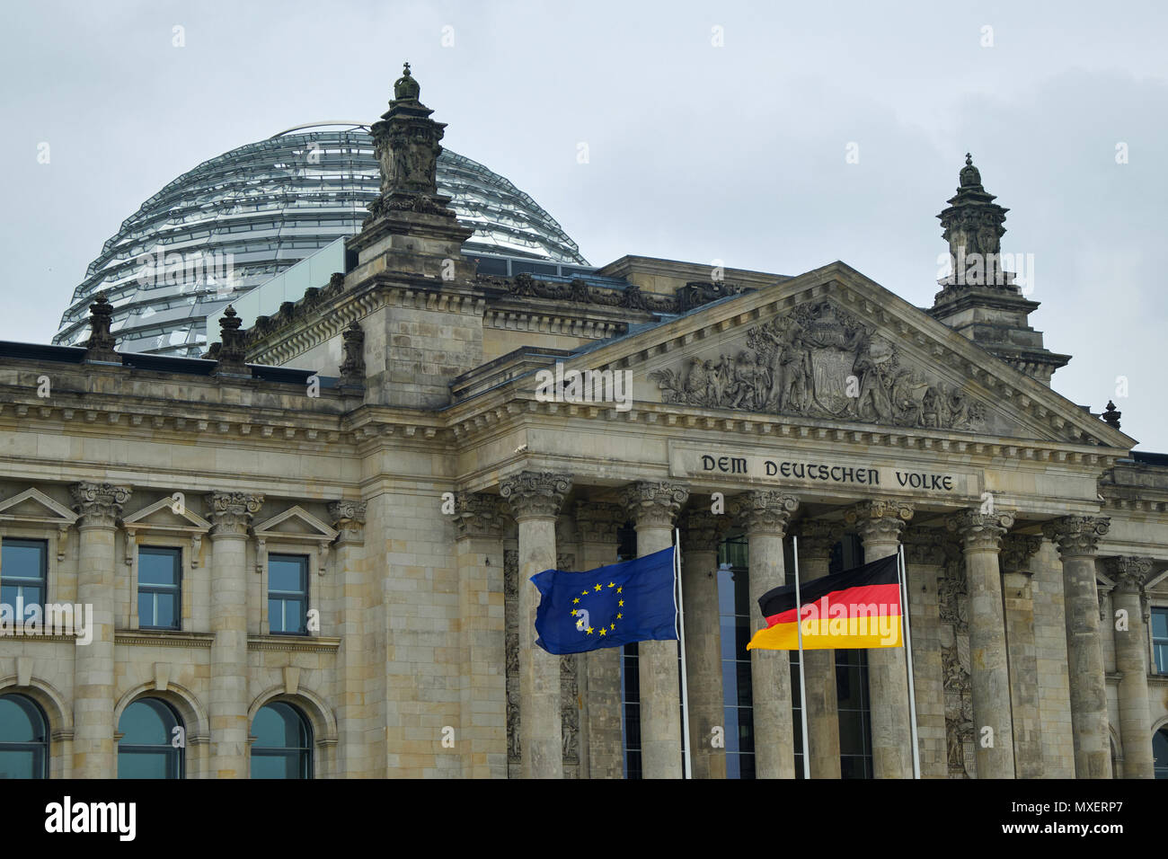 Berlin, Germany - April 14, 2018: Fronton with columns and dome of Reichstag building with German and European Union Flags on the foreground - Stock Image