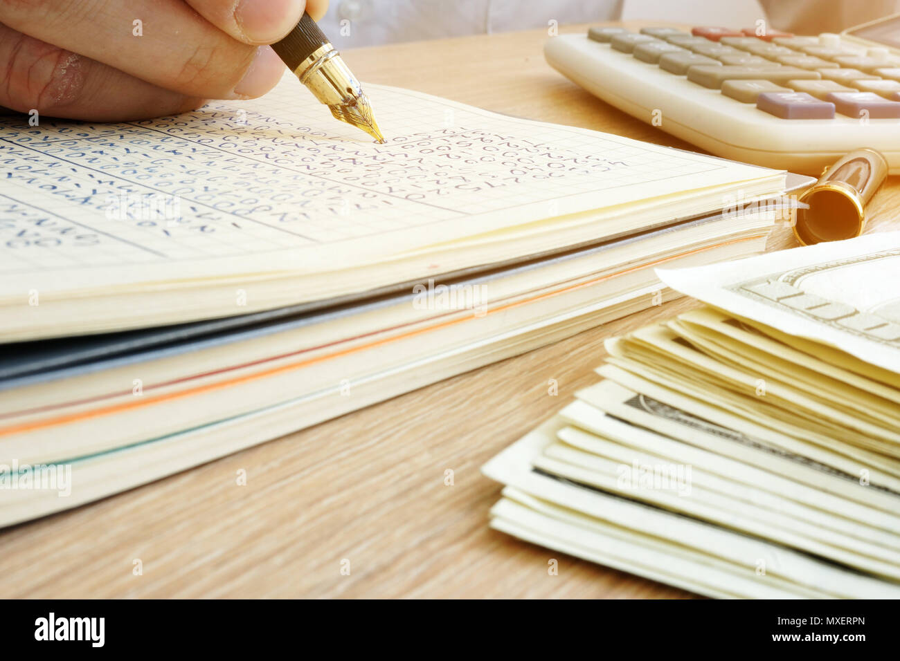Bookkeeper writing business report. Documents, money and calculator. - Stock Image
